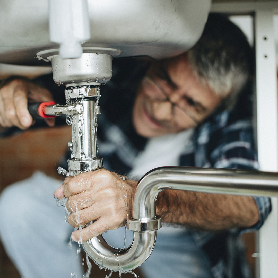 Plumber fixing the kitchen sink